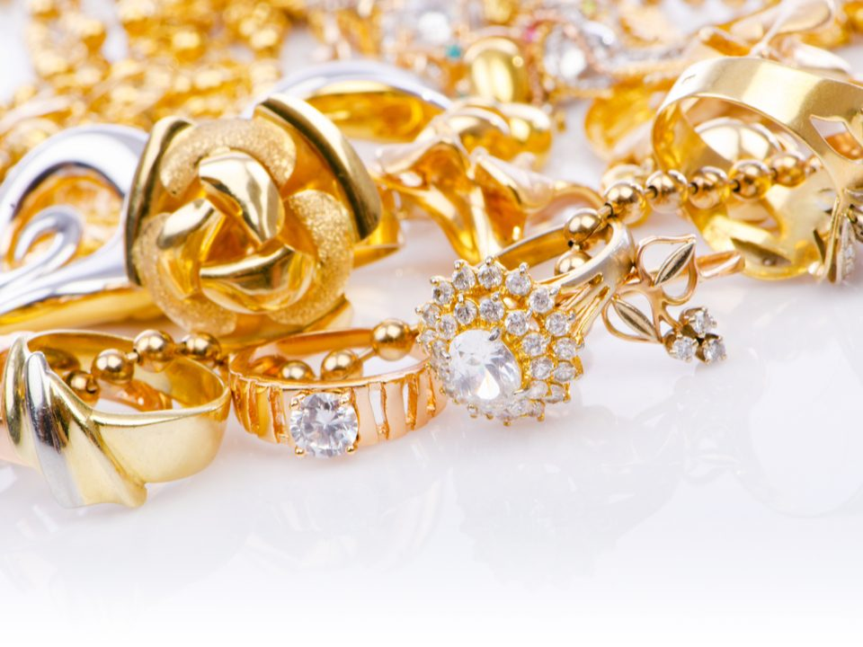 Selection of expensive gold jewellery on a white table